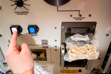 European Space Agency astronaut Samantha Cristoforetti prepares her lunch using the space food rehydrator aboard the International Space Station. © NASA